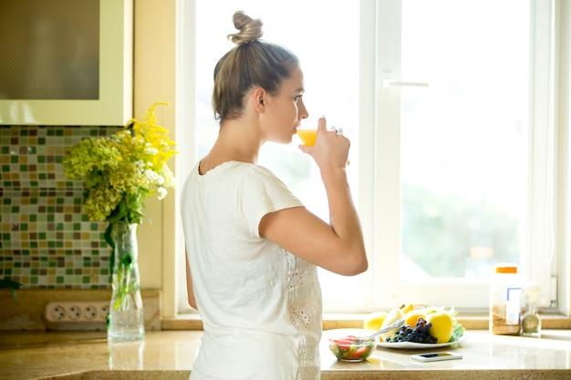 Ritratto di una donna attraente che beve il succo della cucina