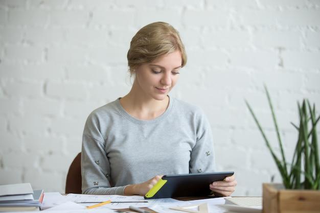 Ritratto di una donna attraente con una tavoletta alla scrivania