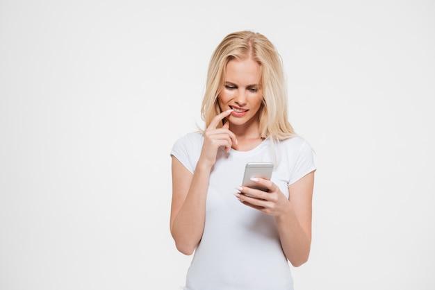 Ritratto di una donna bionda premurosa che per mezzo del telefono cellulare