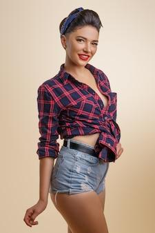 Ritratto di una donna carina con un trucco in pantaloncini di jeans e una camicia in posa nel sorriso carino
