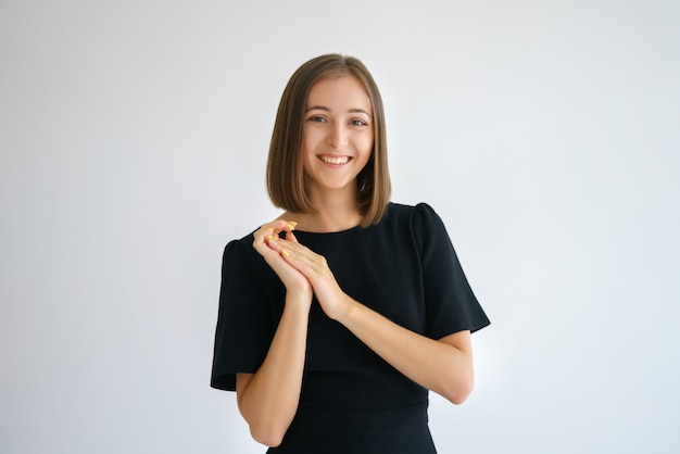Ritratto di una donna carina felice in un abito nero su un muro bianco sorridente