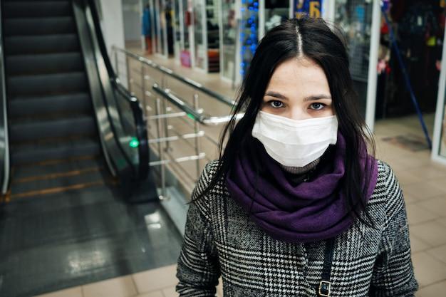 Ritratto di una donna caucasica bianca in una mascherina medica per la protezione contro il coronavirus 2019-ncov