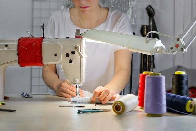 Ritratto di una donna caucasica che lavora a una macchina da cucire.