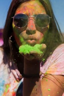 Ritratto di una donna che indossa occhiali da sole che soffia verde polvere di holi