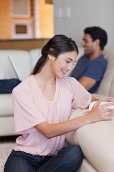 Ritratto di una donna che legge un libro mentre il suo ragazzo sta usando un computer portatile