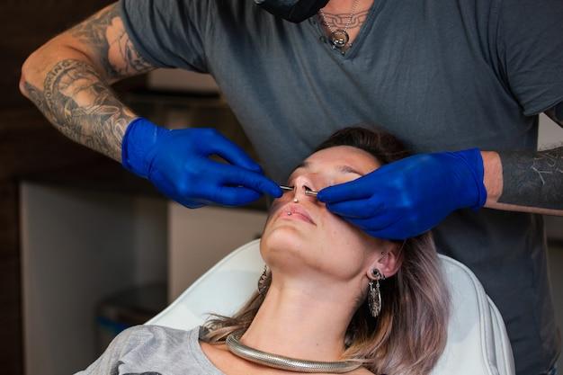 Ritratto di una donna che ottiene il suo naso trafitto. procedura di piercing alla narice
