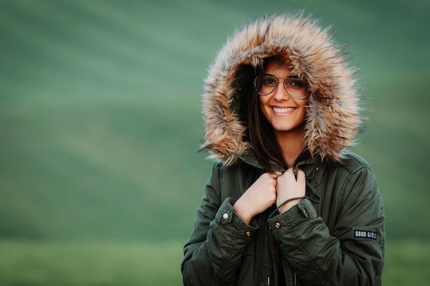 Ritratto di una donna che sente freddo in inverno sul prato verde