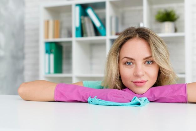 Ritratto di una donna che si appoggia scrivania bianca indossando guanti protettivi