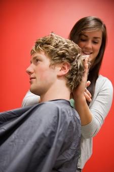 Ritratto di una donna che taglia i capelli di un uomo