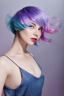Ritratto di una donna con i capelli volanti colorati luminosi, tutte le sfumature del viola. colorazione dei capelli, belle labbra e trucco. capelli che fluttuano nel vento. ragazza sexy con i capelli corti