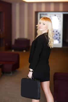 Ritratto di una donna d'affari con una valigetta in ufficio.