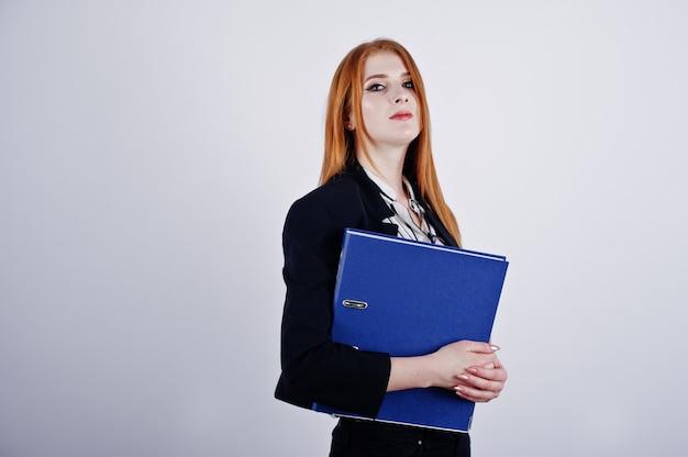 Ritratto di una donna d'affari dai capelli rossi che indossa camicia a righe e una giacca con una cartella blu.