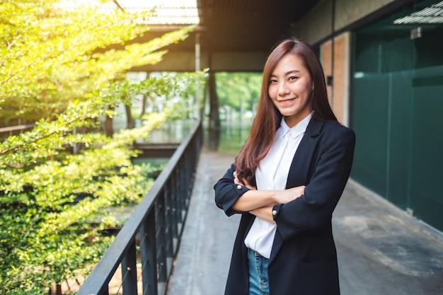 Ritratto di una donna d'affari di successo asiatica in piedi in ufficio