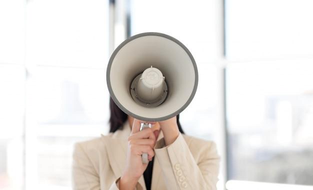 Ritratto di una donna d'affari urlando attraverso il megafono