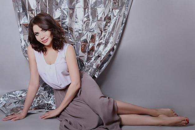 Ritratto di una donna dai capelli castani con un bellissimo trucco professionale su uno sfondo lucido. ragazza sexy con bella pelle pulita e rossetto brillante sulle labbra