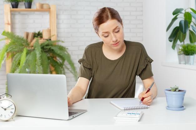 Ritratto di una donna di affari casuale felice che si siede nel suo luogo di lavoro in ufficio