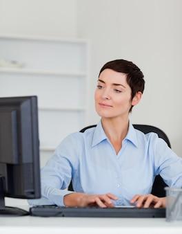 Ritratto di una donna di affari seria che scrive con il suo computer