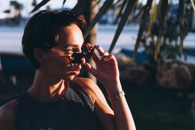 Ritratto di una donna dietro le foglie di palma