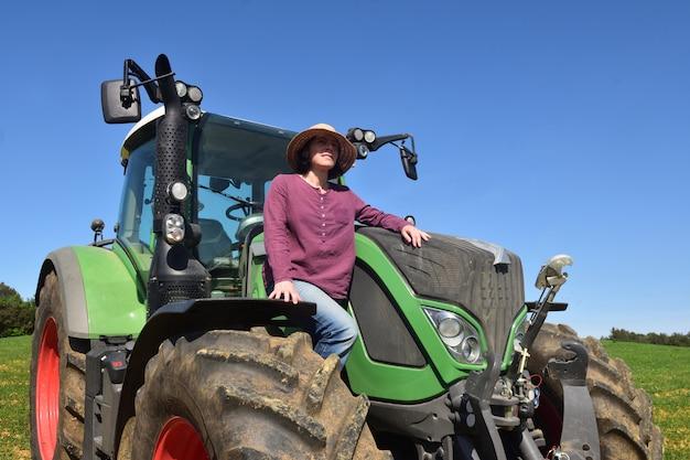 Ritratto di una donna e un trattore dell'agricoltore sul campo