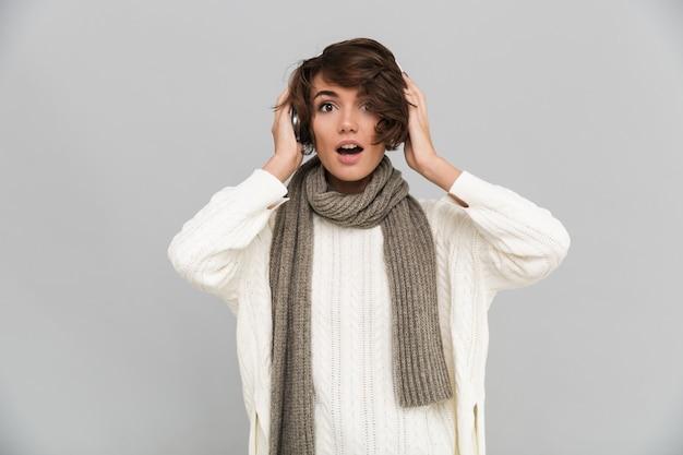 Ritratto di una donna eccitata in sciarpa ascoltando musica