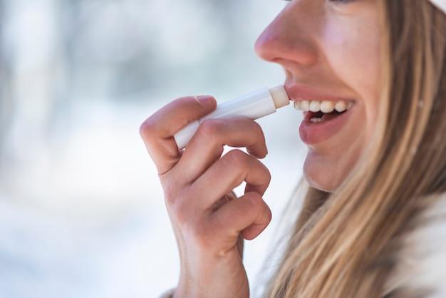 Ritratto di una donna felice che applica balsamo per le labbra in inverno con una montagna innevata