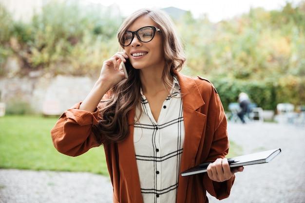 Ritratto di una donna felice che parla sul telefono cellulare