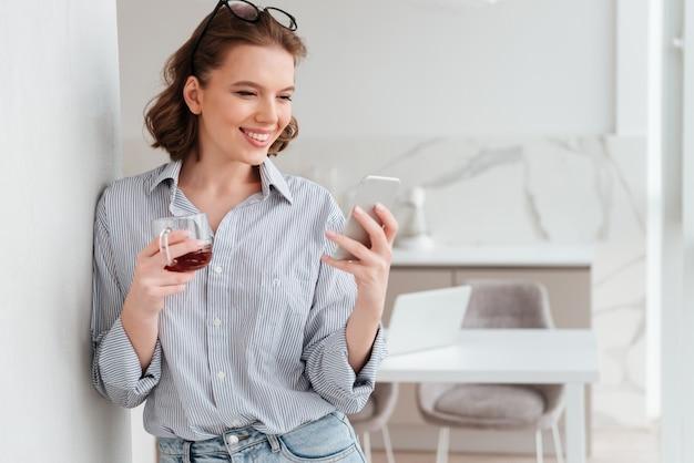 Ritratto di una donna felice che per mezzo del telefono cellulare
