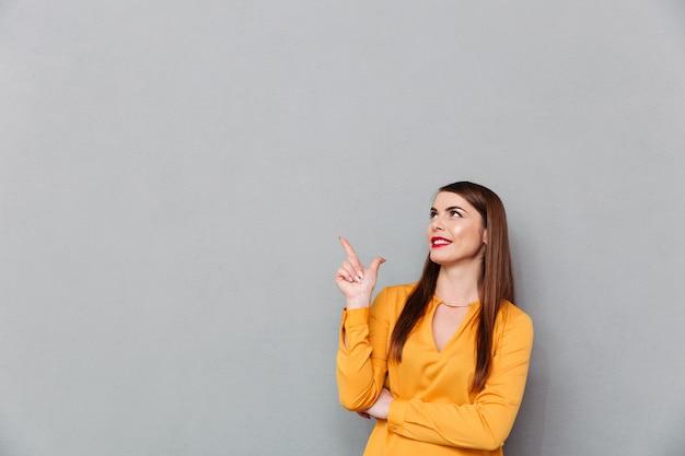 Ritratto di una donna felice che punta il dito verso l'alto