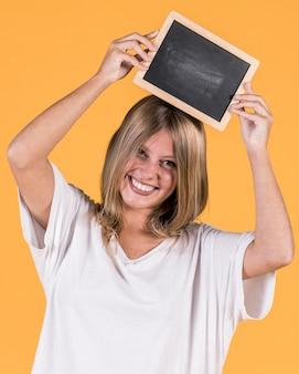 Ritratto di una donna felice che tiene ardesia in bianco sopra la sua testa