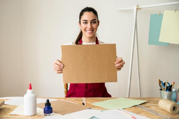 Ritratto di una donna felice che tiene carta marrone a mano
