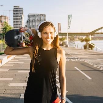 Ritratto di una donna felice con skateboard ascoltando musica in cuffia