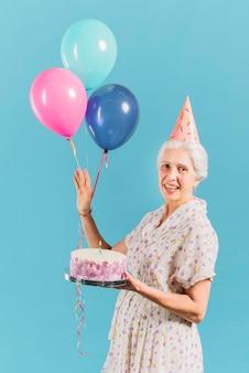 Ritratto di una donna felice con torta di compleanno e palloncini su sfondo blu