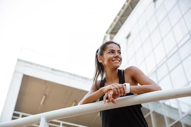 Ritratto di una donna felice di forma fisica che si appoggia su una ferrovia