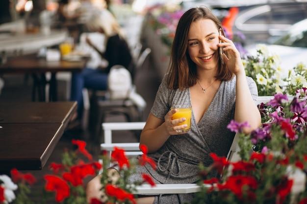 Ritratto di una donna felice in un caffè con telefono e succo