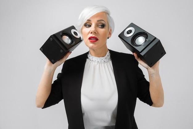 Ritratto di una donna fiduciosa in una tuta con altoparlanti nelle sue mani isolato su uno sfondo chiaro