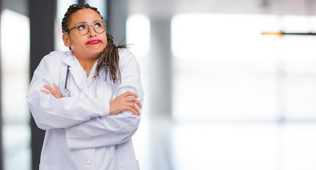 Ritratto di una donna giovane medico nero dubitando e alzando le spalle le spalle