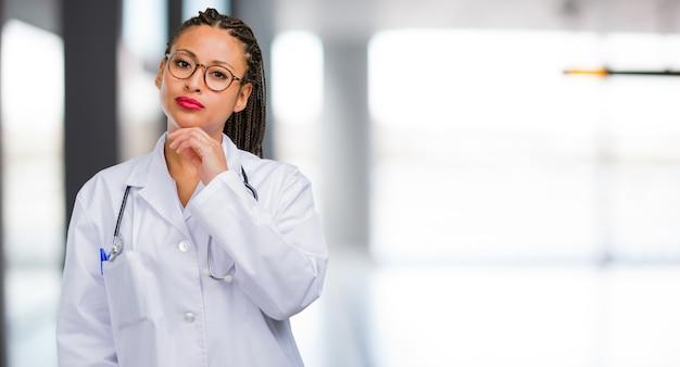 Ritratto di una donna giovane medico nero pensando e alzando lo sguardo