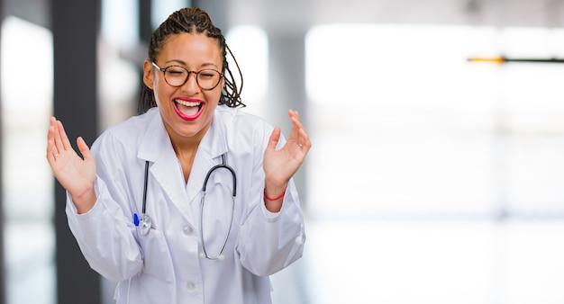 Ritratto di una donna giovane medico nero ridendo e divertendosi