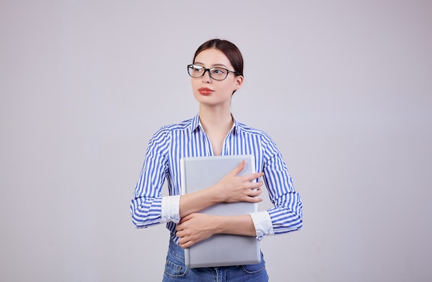 Ritratto di una donna impegnata in una camicia a strisce bianco-blu con gli occhiali e un computer portatile su grigio. dipendente dell'anno, signora d'affari.