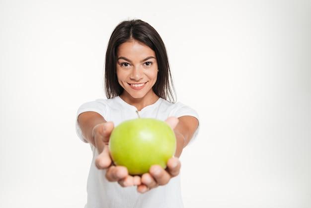 Ritratto di una donna in buona salute sorridente che mostra mela verde