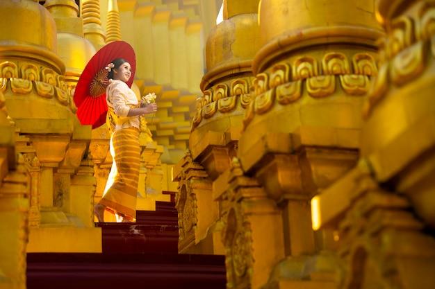 Ritratto di una donna in costume nazionale birmano in piedi con un ombrello rosso in mezzo a molte pagode dorate