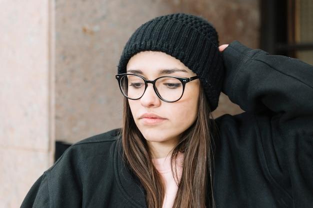 Ritratto di una donna in occhiali e cappello a maglia