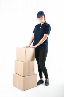 Ritratto di una donna in piedi con la pila di scatole di cartone