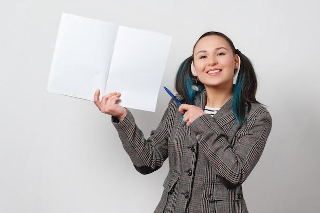Ritratto di una donna, in possesso di un quaderno con un copyspace e mostra la penna.