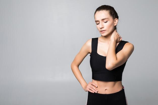 Ritratto di una donna in un'attrezzatura di forma fisica che avverte dolore al collo, alla spalla e alla schiena isolato sulla parete bianca