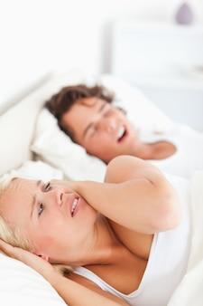 Ritratto di una donna infastidita svegliata dal russare del suo fidanzato