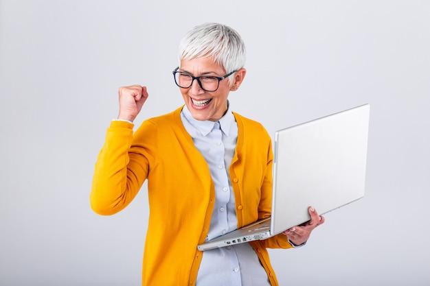 Ritratto di una donna matura allegra con un computer portatile e celebrando il successo isolato su sfondo grigio.