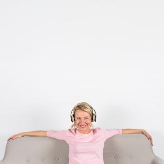 Ritratto di una donna matura bionda felice che si siede sulla musica d'ascolto del sofà sulla cuffia contro fondo bianco