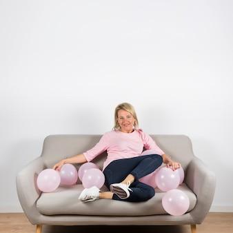 Ritratto di una donna matura sorridente che si siede sul divano con palloncini rosa a casa