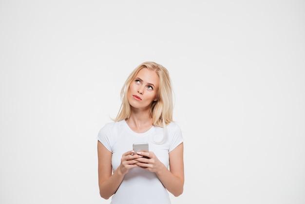 Ritratto di una donna pensierosa tenendo il telefono cellulare